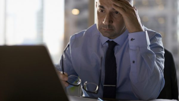 Stressed male lawyer working late at laptop
